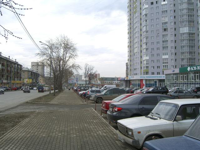 Автостоянка отделяет тротуар от застройки.