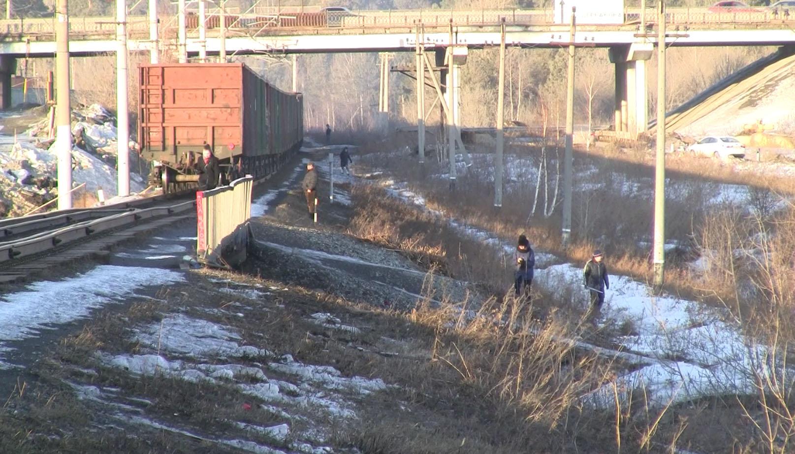 Пешеходы пережидают поезд, чтобы продолжить движения вдоль железной дороги