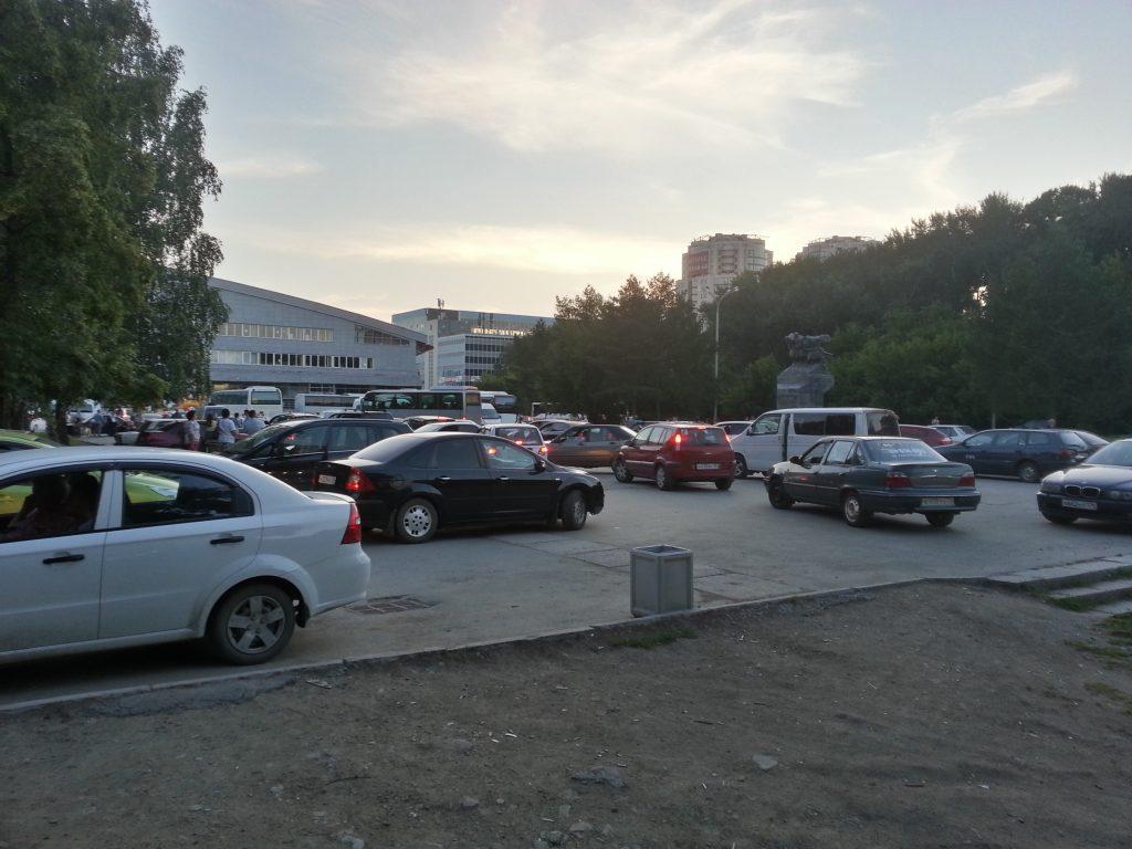 Площадь перед памятником воинам-спортсменам заставлена машинами во время концерта во Дворце Спорта.