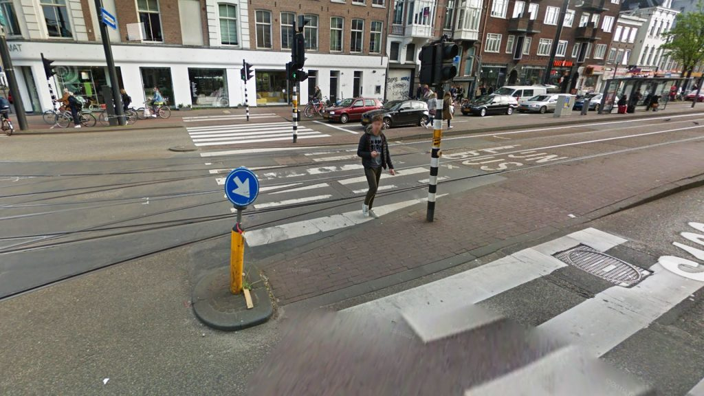 "Островок безопаснсти со знаком ""объезд препятствия справа"" перед трамвайной платформой в Амстердаме."